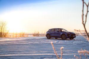 Seitenansicht eines Porsche Macan vor einer Winterlandschaft.