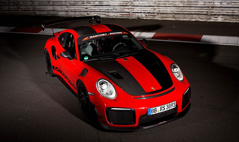 Roter Porsche 911 GT2 RS MR mit schwarzen Streifen von schräg oben rechts vorne, nachts auf Rennstrecke stehend