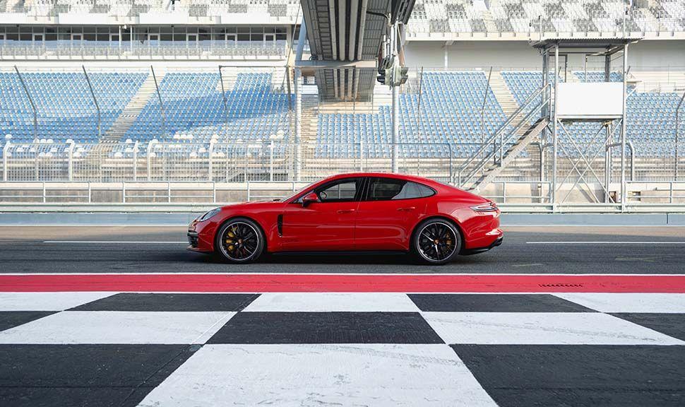 Roter Porsche Panamera GTS linke Seitenansicht, stehend, auf Rennstrecke