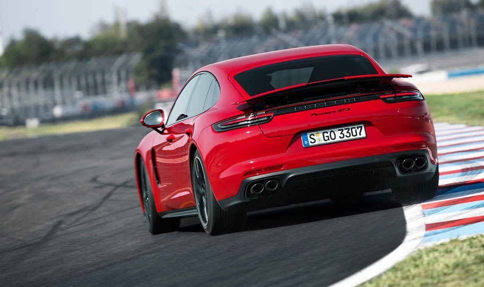 Roter Porsche Panamera GTS beschleunigt leicht querstehend aus Kurve auf Rennstrecke heraus