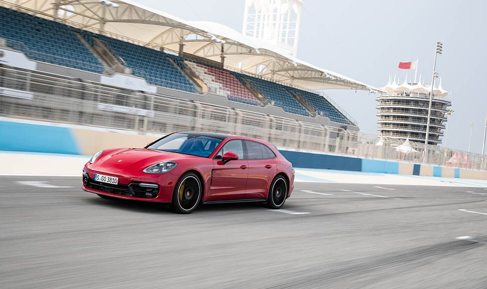 Roter Porsche Panamera Sport Turismo GTS auf Rennstrecke fahrend