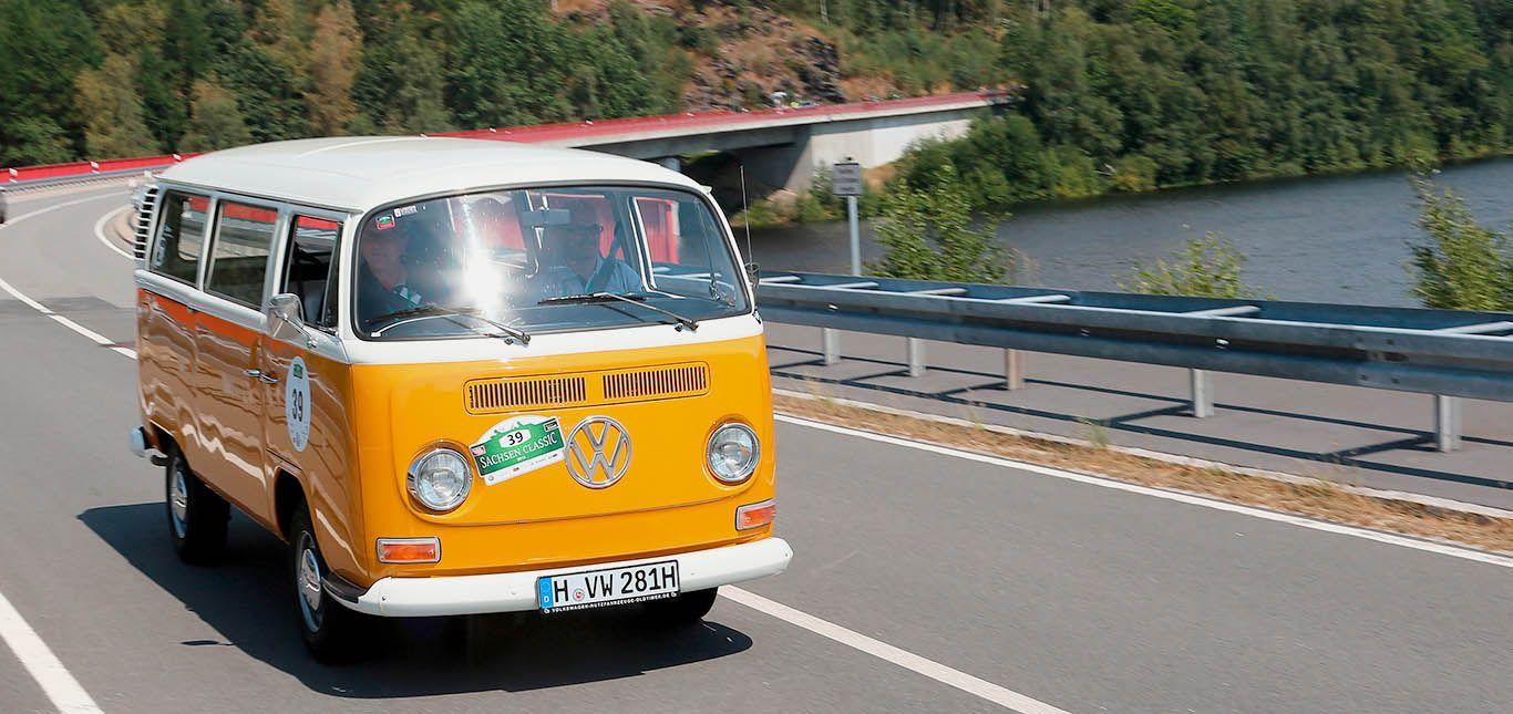 Gelb-weißer VW T2 fährt über Brücke