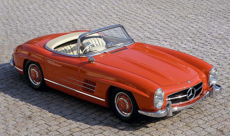 Roter Mercedes 300 SL Roadster mit offenem Verdeck auf Kopfsteinpflaster stehend, von oben