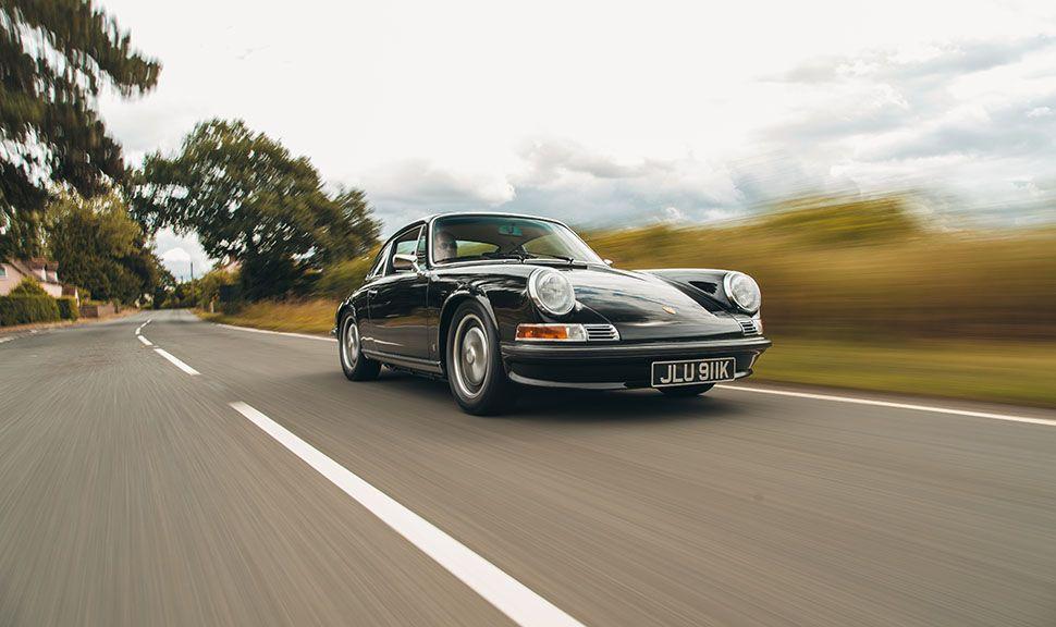 Schwarzer Porsche 911 fährt auf Landstraße, schräg rechts vorne