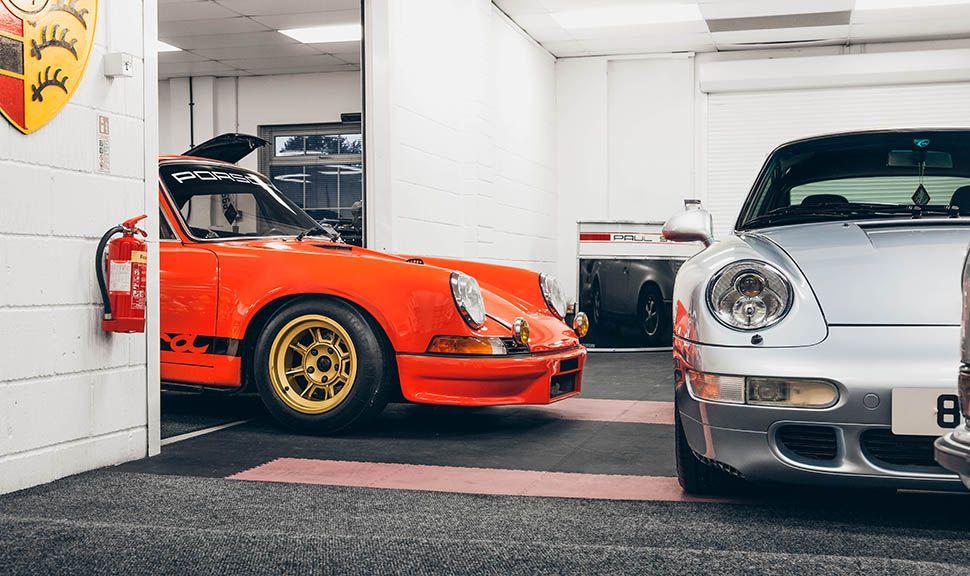 Oranger und silberner Porsche 911 im Anschnitt im Showroom von Paul Stephens