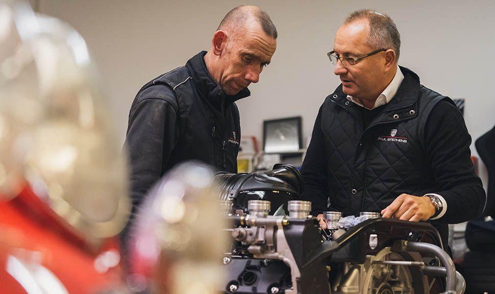 Paul Stephens im Gespräch mit Kollegen, im Vordergrund ein in Wartung befindlicher Motor