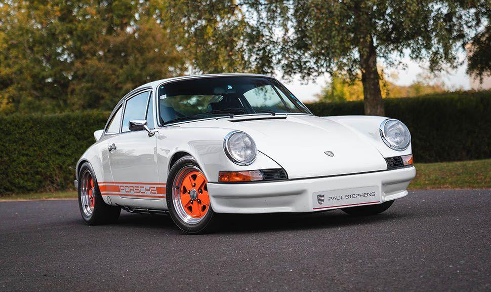 Weißer Porsche 911 mit orangen Felgen und Seitenstreifen