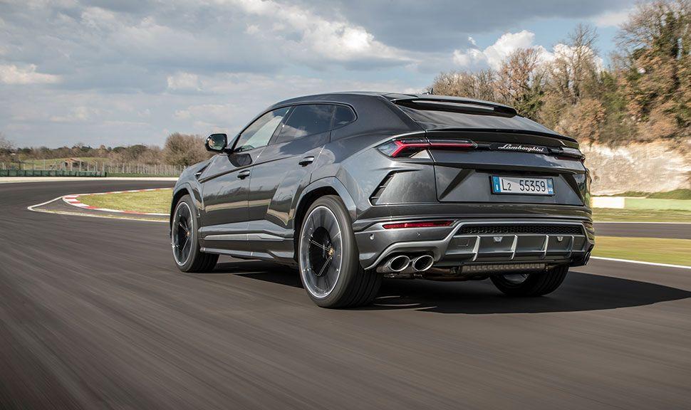 Lamborghini Urus, durch Landschaft fahrend, schräg links hinten