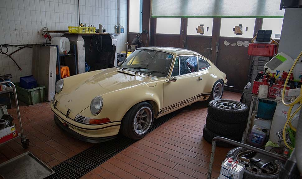 Elfenbeinweißer Porsche 911 G-Modell in Werkstattgarage