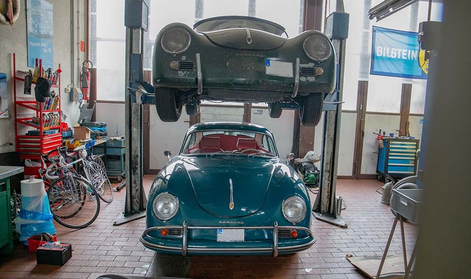 Zwei Porsche 356 übereinander. Der obere auf einer Hebebühne.