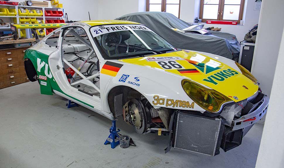 Aufgebockte Karosserie des Porsche 996 GT3 RSR, ohne Räder und Stoßstangen, von schräg rechts vorne