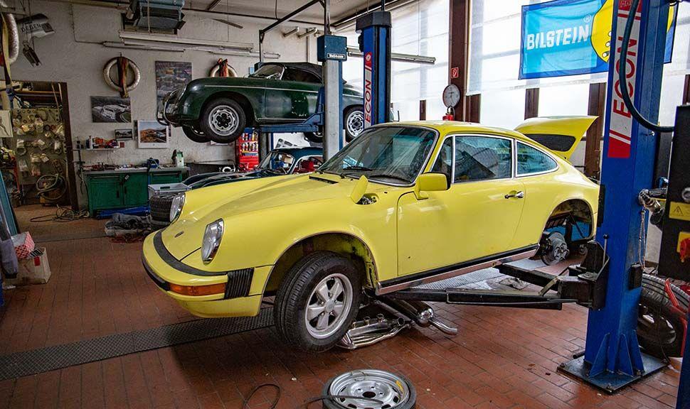 Gelber Porsche 911 auf Hebebühne