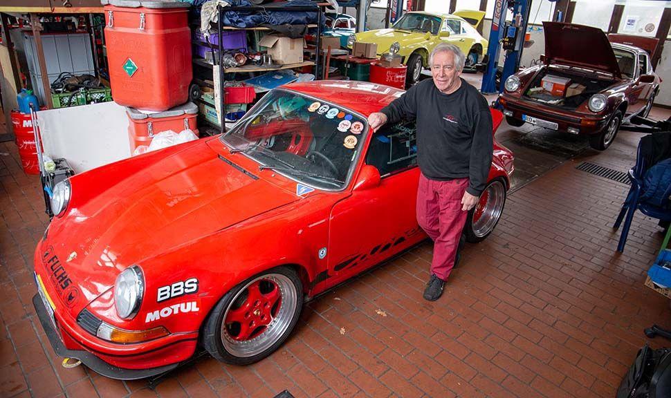 Herwig Roitmayer vor seinem roten Porsche 911 Carrera RSR in seiner Werkstatt