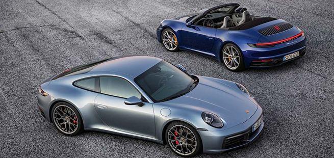 Silbernes Porsche 911 Coupé gegenläufig zu blauem Porsche 911 Cabrio geparkt