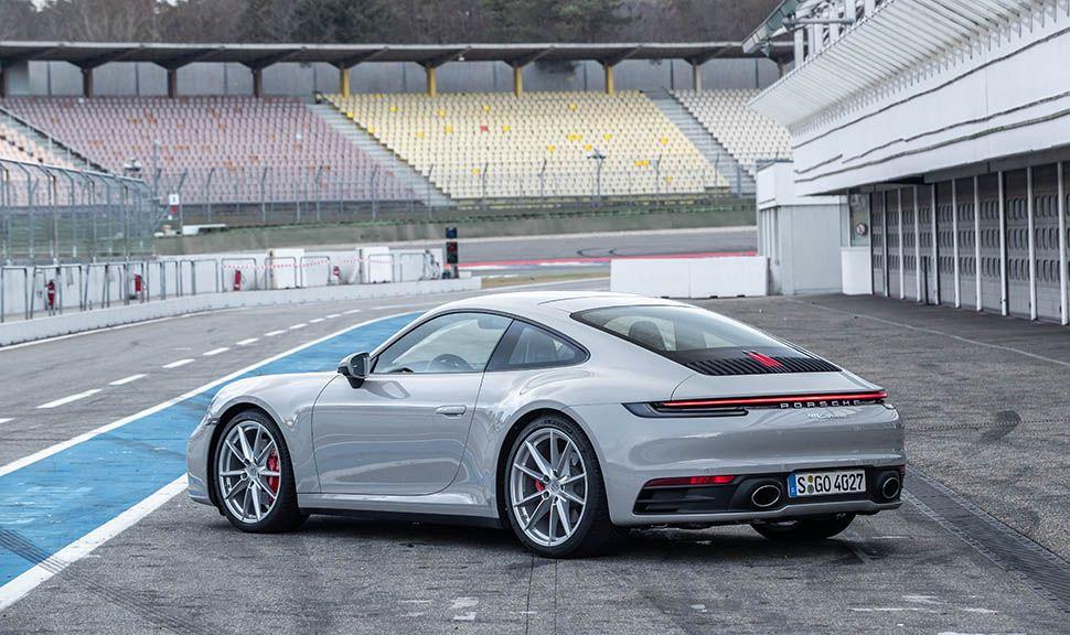 Silberner Porsche 911 schräg links hinten in Boxengasse stehend