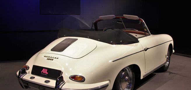 Elfenbeinweißer Porsche 356 mit schwarzem, offenem Verdeck, schräg rechts hinten in Garage