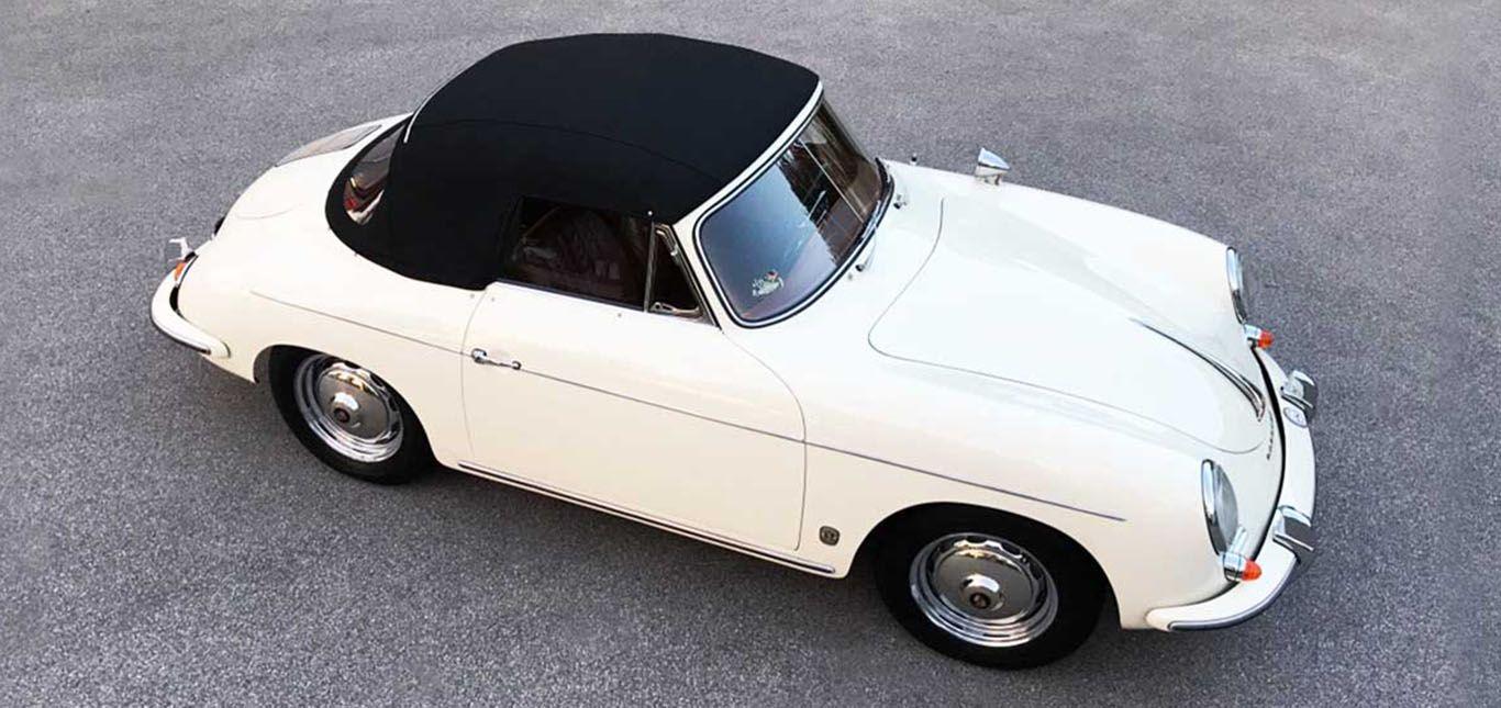 Elfenbeinweißer Porsche 356 B Cabrio mit schwarzem, geschlossenem Verdeck, parkend