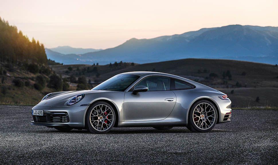 Silberner Porsche 911 seitlich in Dämmerung stehend, Berge im Hintergrund