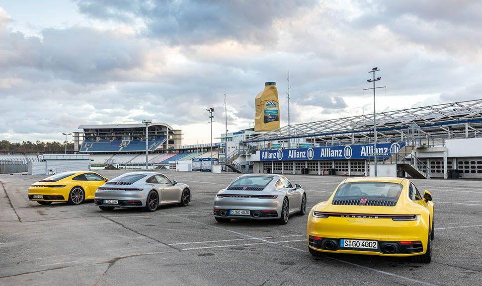Vier Porsche 911 von hinten, nebeneinander auf Rennstrecke stehende