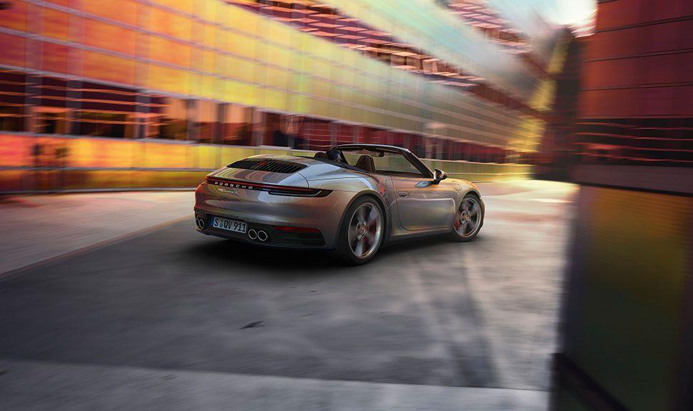 Silbernes Porsche 911 Cabrio schräg rechts hinten vor futuristischer Kulisse