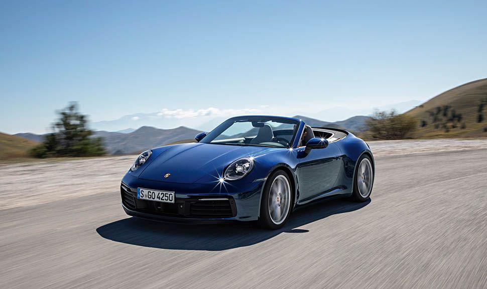 Dunkelblaues Porsche 911 Cabrio fährt auf Landstraße, Berghorizont