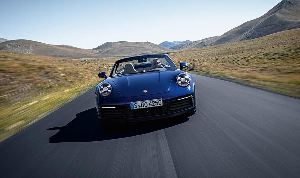 Dunkelblaues Porsche 911 Cabrio fährt auf Landstraße, Frontalaufnahme