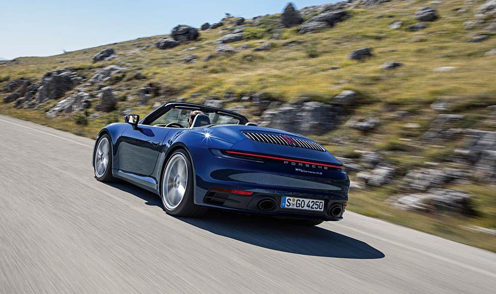 Dunkelblaues Porsche 911 Cabrio auf Landstraße fahrend, schräg links hinten