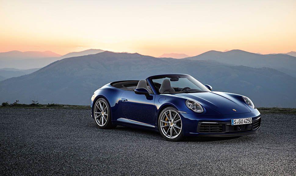 Dunkelblaues Porsche 911 Cabrio von schräg rechts vorne vor Bergen