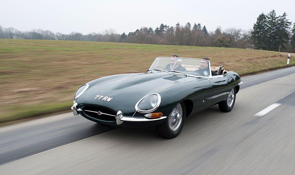 dunkelgrünes Jaguar E-Type Cabrio auf Landstraße fahrend, Rechtslenker, schräg links vorne