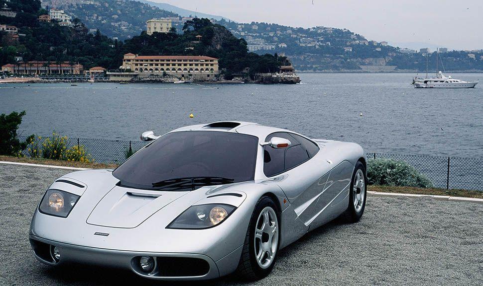 Silberner McLaren F1 schräg links vorne, an Küste stehend, Villa am anderen Ufer, dazwischen Motoryacht
