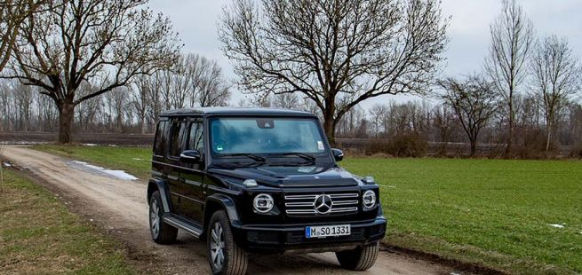 Schwarzer Mercedes G500 von schräg rechts vorne, auf Feldweg stehend