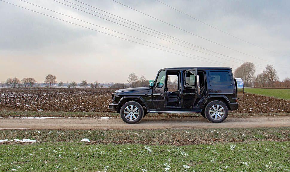 Schwarzer Mercedes G500 von links mit offenen Türen