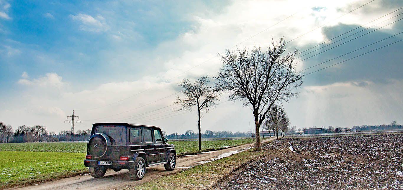 Schwarzer Mercedes G500 von schräg rechts hinten, auf Feldweg stehend