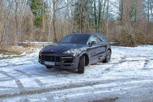 Schwarzer Porsche Cayenne Turbo auf verschneitem Seeparkplatz