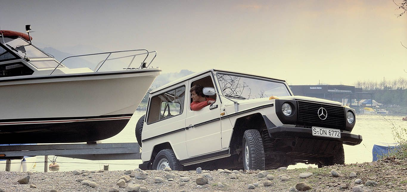 Klassische Mercedes G-Klasse in Weiß zieht Boot auf Anhänger Hang hinauf
