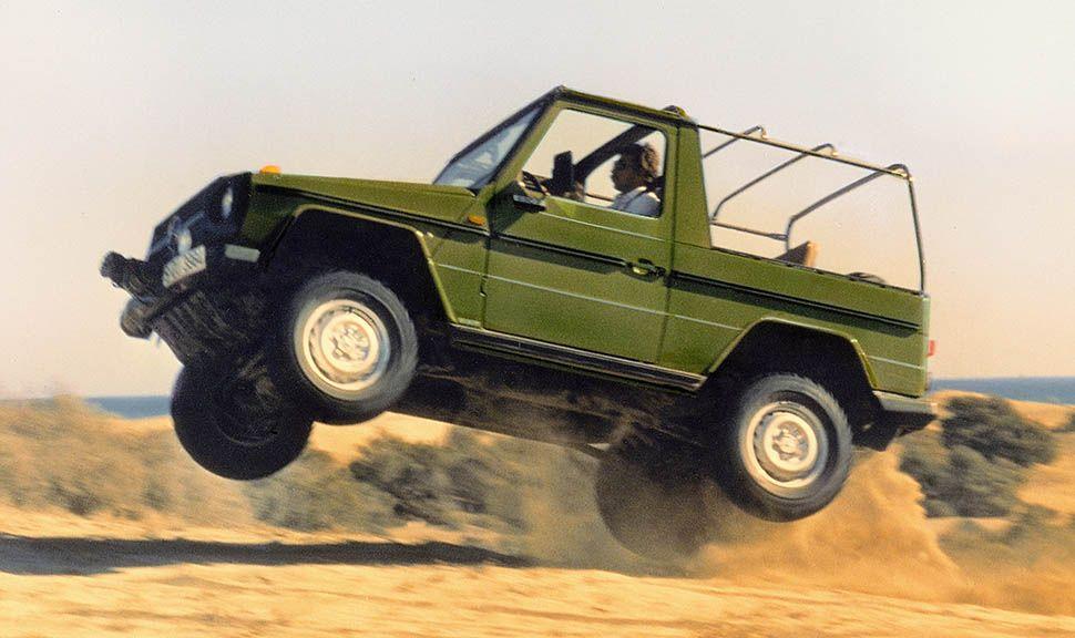 Olivgrüne Mercedes G-Klasse springt in Dünensand