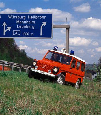Feuerwehrauto auf Basis der Mercedes G-Klasse steht am schrägen Hang neben einer Autobahn