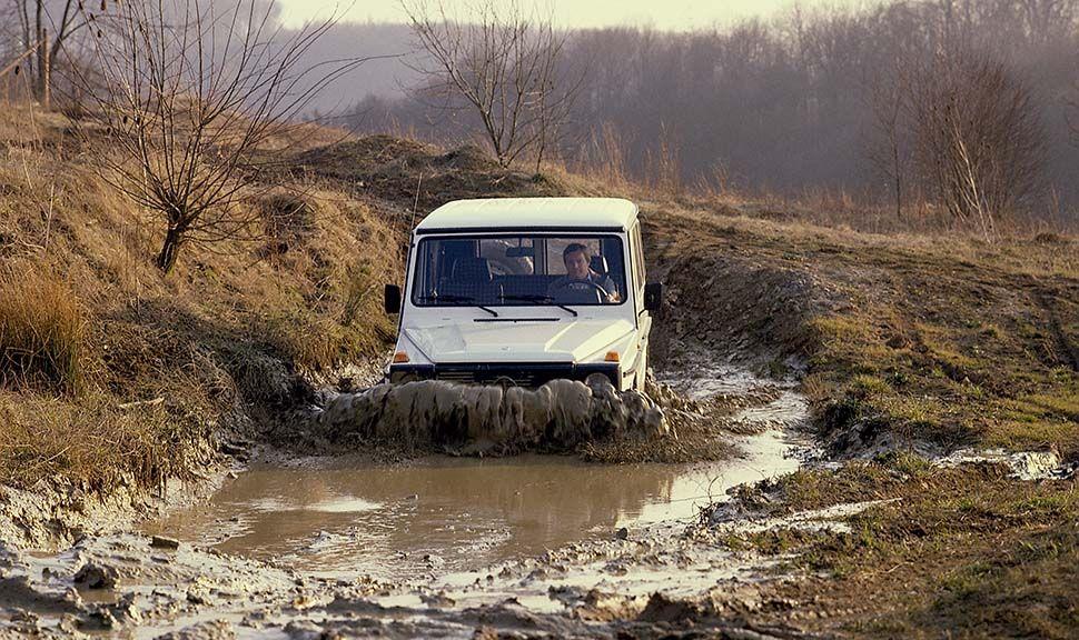 Weiße Mercedes G-Klasse fährt durch Schlammwasser