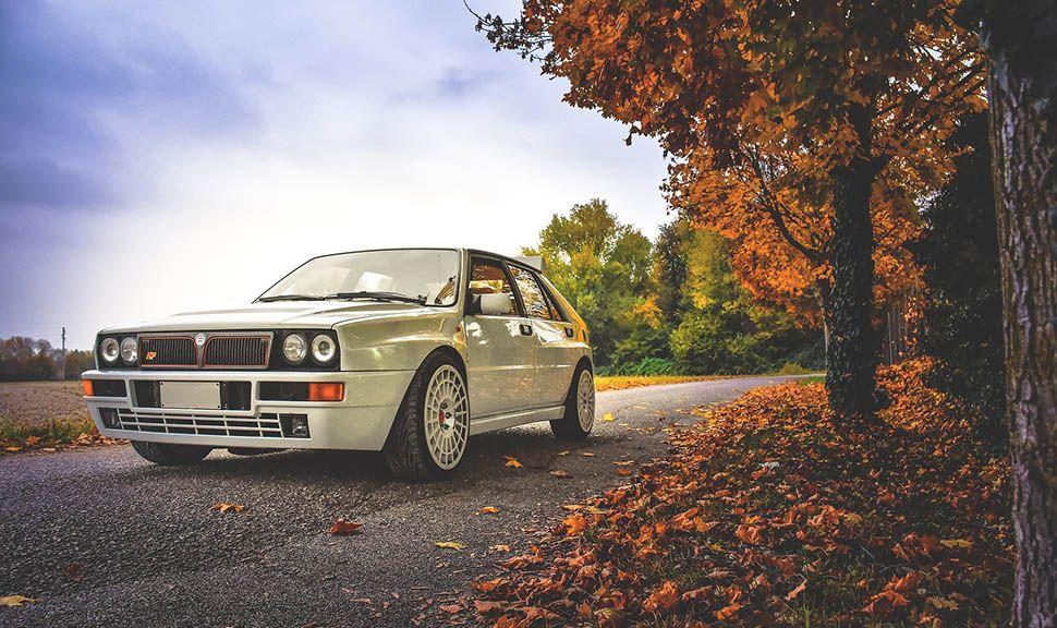 Weißer Lancia Delta HF Integrale von links schräg vorne auf herbstlicher Straße stehend