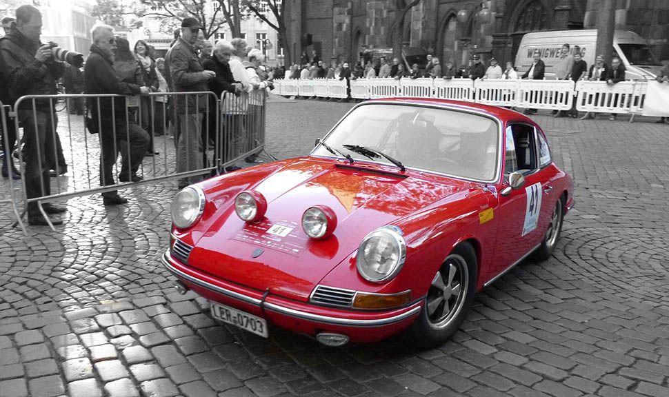 Roter Porsche 911 fährt bei einer Oldtimer-Rallye