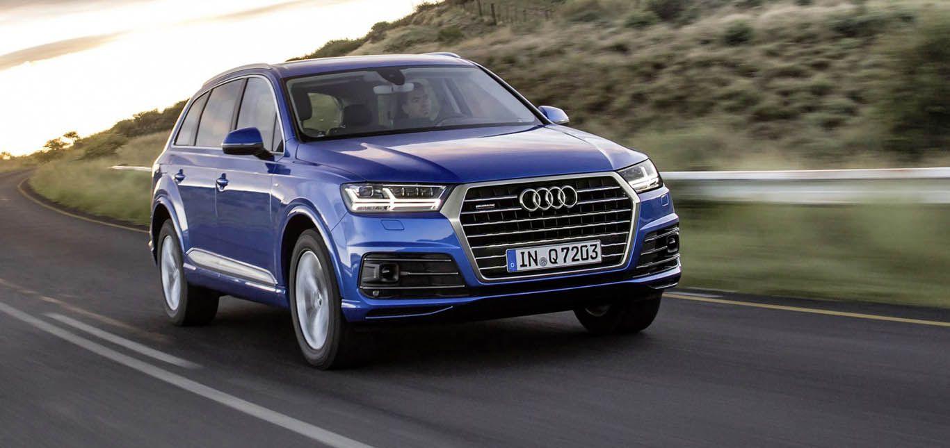 Blauer Audi Q7 fährt auf Landstraße, schräg rechts vorne