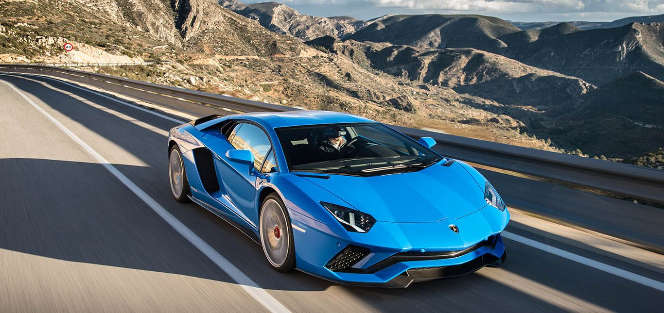 Blauer Lamborghini Aventador S fährt in den Bergen
