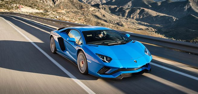 Blauer Lamborghini Aventador S fährt auf Bergstraße