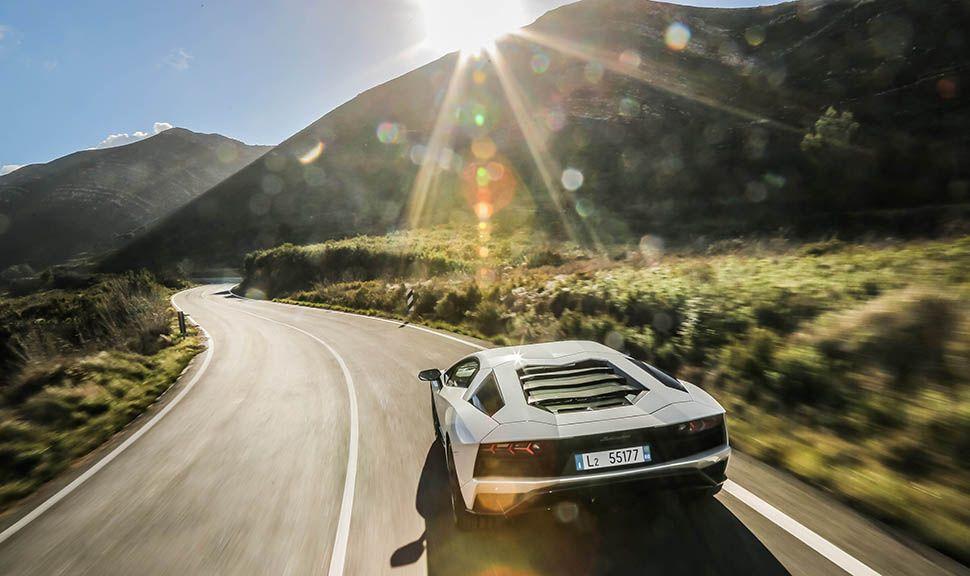 Weißer Lamborghini Aventador S fährt der Sonne entgegen