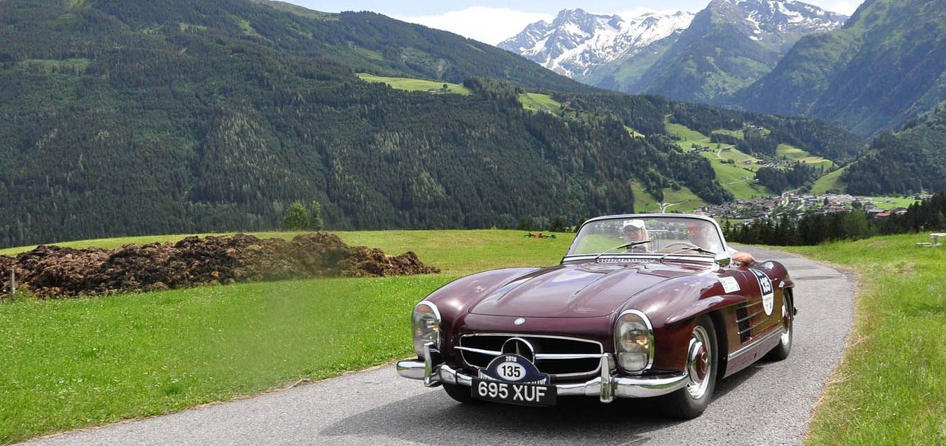 Weinroter Mercedes-Benz 300 SL Roadster fährt bei Kitzbühel Alpenrallye in Berglandschaft
