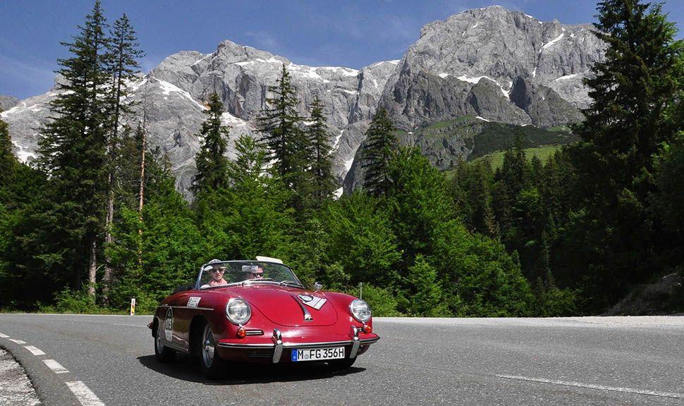 Roter Porsche 356 Cabrio fährt auf Berglandstraße bei Kitzbüheler Alpenrallye
