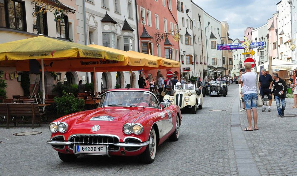 Rote Corvette, beiger BMW Oldtimer fahren in Altstadt