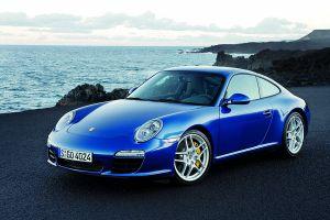 Blauer Porsche 911 997 von schräg links vorne am Meer stehend