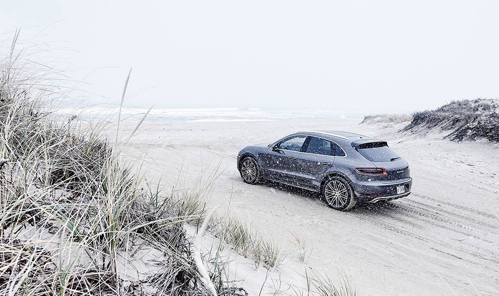 Grauer Porsche Macan Turbo am Strand