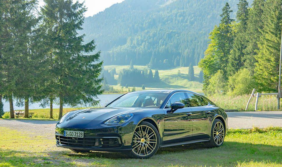 Dunkelblauer Porsche Panamera von schräg links vorne vor Bergsee